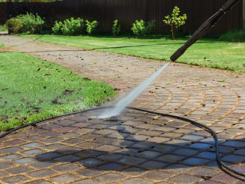 Cleaning street with high pressure power washer, washing stone garden paths