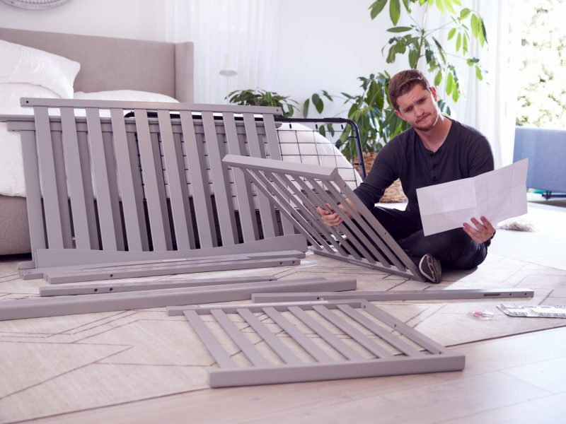 Confused Father To Be Looking At Instructions For Self Assembly Baby Cot