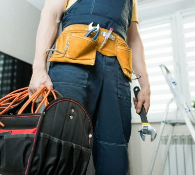 Close-up of unrecognizable handyman with bag of work tools standing in modern apartment and holding wrench