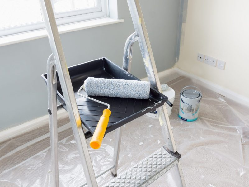 Painting and decorating with a roller and tray on a set of metal step ladders with cans of paint and a dust sheet in the background